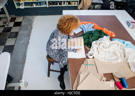 High angle view of mature female fashion designer drawing in sketchbook at workshop table - Stock Photo