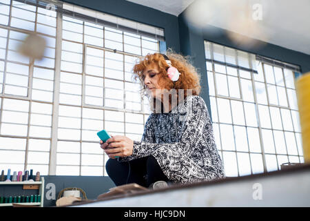Mature female fashion designer listening to smartphone music in workshop - Stock Photo