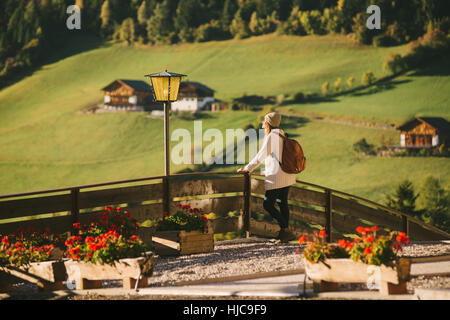 Woman enjoying view by wooden fence, Santa Maddalena, Dolomite Alps, Val di Funes (Funes Valley), South Tyrol, Italy - Stock Photo
