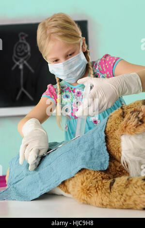 Girl pretending to be vet giving toy tiger syringe injection during operation - Stock Photo