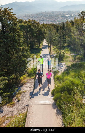Young men and women running in park, Split, Dalmatia, Croatia - Stock Photo