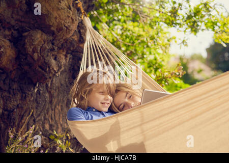 Teenage boy and brother reclining in garden hammock browsing digital tablet - Stock Photo