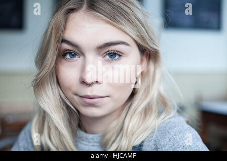 Portrait of young woman, in cafe - Stock Photo