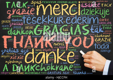 Hand writing 'Thank you' in many languages on a chalkboard - Stock Photo
