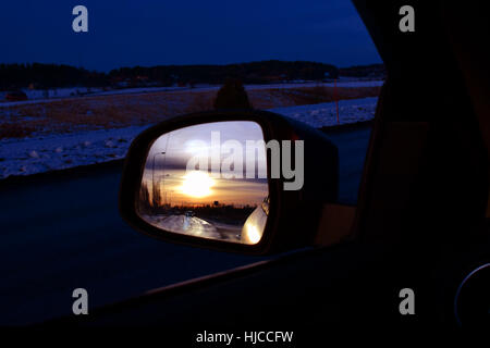 Sunset reflected in car side-view mirror. - Stock Photo