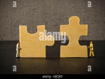 little people solving the problem with the puzzle - Stock Photo