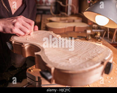 Woman violin maker, luthier, at work in her laboratory in Cremona, Italy - Stock Photo