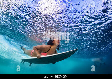 Active girl in action. Surfer woman with surf board dive underwater under breaking ocean wave Water sport, extreme - Stock Photo