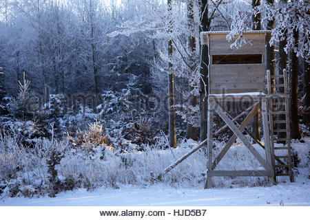 A hunter's hideout for the shooting season is covered in snow on a beautiful winter's day in the south of Bavaria, - Stock Photo