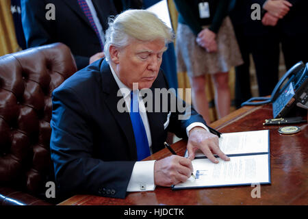 Washington, USA. 24th Jan, 2017. US President Donald Trump signs one of five executive orders related to the oil - Stock Photo