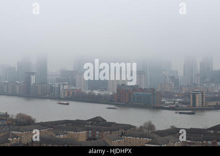 London, UK. 25th January, 2017. UK Weather: Heavy fog continues over London and Canary Wharf business park buildings - Stock Photo