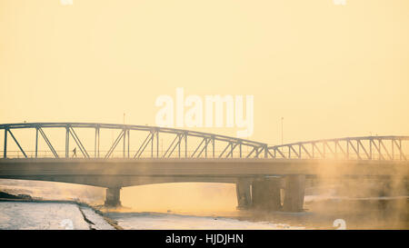 Winter season, city bridge under the fog. - Stock Photo