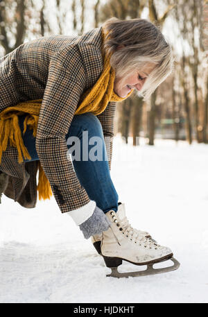 Senior woman in winter clothes putting on old ice skates. - Stock Photo