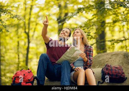 Blond girl in checkered shirt and bearded man with backpacks seating on the rock in the forest - Stock Photo