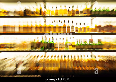 An abstract with motion blur of whiskey/whisky bottles on the shelves of an Irish whiskey bar in Killarney, Kerry - Stock Photo