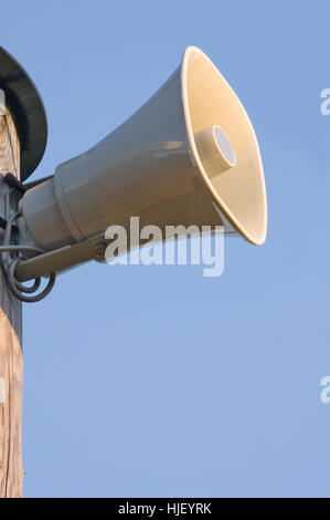 Gray plastic horn loudspeaker pole post, blue sky vertical background - Stock Photo