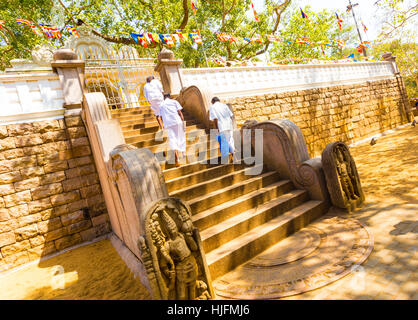 People walking past carved moonstone at base of steps to Jaya Sri Maha Bodhi containing the sacred fig tree of enlightenment - Stock Photo