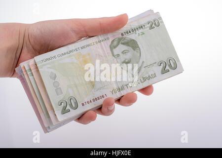 Hand holding Turksh Lira banknotes  on white background - Stock Photo