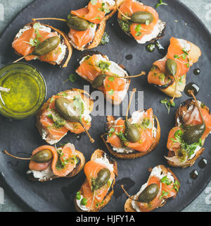 Homemade salmon crostini with cream-cheese, watercress, capers and pesto suace - Stock Photo