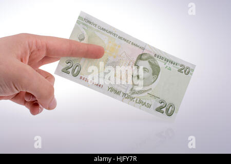 Hand holding Turksh Lira banknote  on white background - Stock Photo