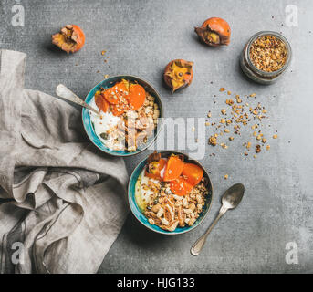 Oatmeal, quinoa granola with yogurt, dried fruit, seeds, honey, persimmon - Stock Photo