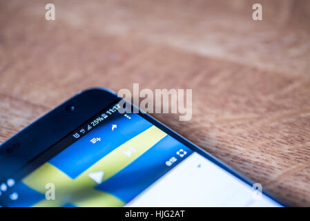 Smartphone on wooden background with 4G network sign 25 per cent charge and Sweden flag on the screen. - Stock Photo