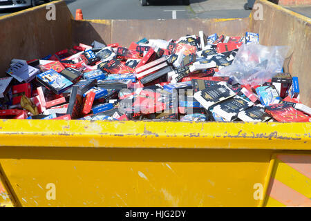 An industrial sized skip full of a huge collection of old obsolete VHS video tapes - Stock Photo