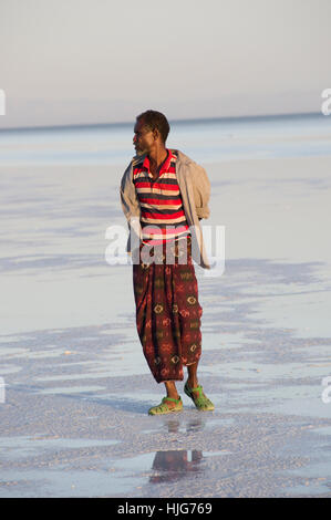 Afar man, face turned away, standing on the shallow water of the salt flats in Dallol, Danakil Depression, Ethiopia - Stock Photo