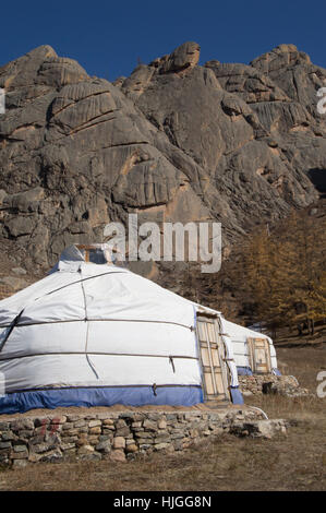 Two Mongolian gers or yurts made from white and blue canvas with paneled doors and stone foundations. Rugged mountains - Stock Photo