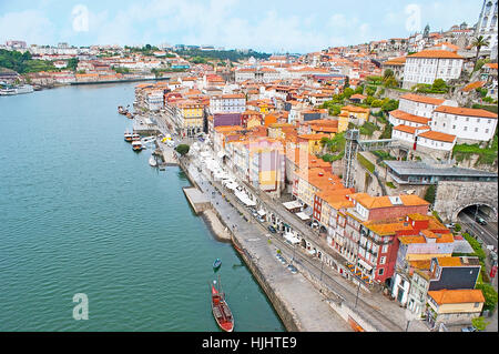 PORTO, PORTUGAL - APRIL 30, 2012: The Ribeira embankment with numerous cafes and wine houses, Rabelo boats and residential - Stock Photo