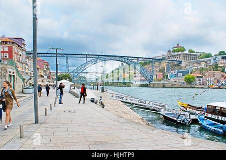 PORTO, PORTUGAL - APRIL 30, 2012: The walk along Ribeira promenade of Douro River with a view on Luis I Bridge and - Stock Photo