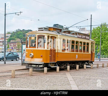 PORTO, PORTUGAL - APRIL 30, 2012: The vintage tram waits for the tourists at the station with the Douro River embankment - Stock Photo