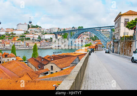 PORTO, PORTUGAL - APRIL 30, 2012: The rwalk along the hilly street in Vila Nova de Gaia with a view on roofs of - Stock Photo