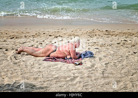 Plus sized obese and overweight woman wearing a bikini and sunbathing on the beach. - Stock Photo