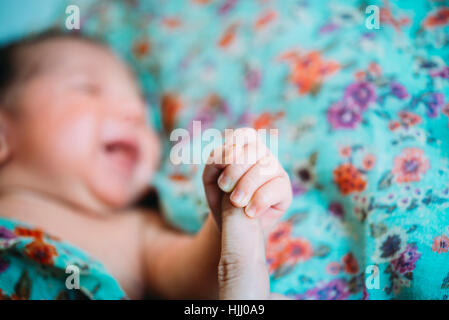 Newborn baby girl holding mother's finger - Stock Photo