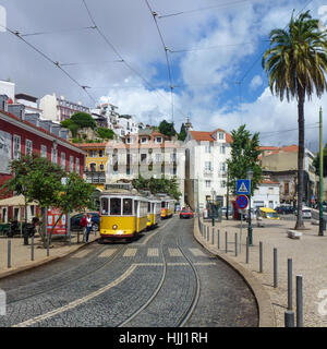 Yellow tram on a cobbled street in Lisbon, Portugal - Stock Photo
