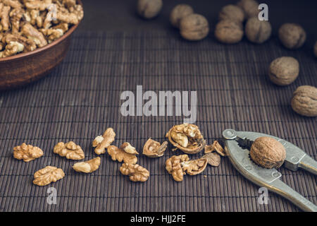 Walnut kernels and whole walnuts in brown ceramic bowl. Healthy organic food concept. Selective focus - Stock Photo