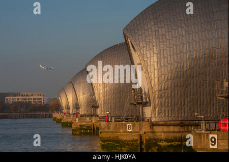 The thames Barrier at Woolwich Kent. in evening light. with a plane coming into the london city airport - Stock Photo