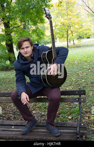 Young man with an acoustic guitar, Selective focus and small depth of field, lens flare - Stock Photo