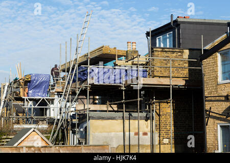 Scaffolding to a two new dormer / dormers / dormas / dorm on the roof / roofs of Victorian terraced house / houses. - Stock Photo