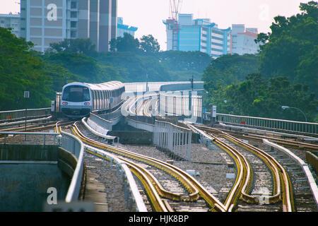 Singapore MRT train on a railroad at sunset - Stock Photo