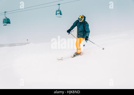 Skier man skiing on ski slope - Stock Photo