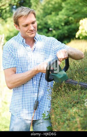 Man Cutting Garden Hedge With Electric Trimmer - Stock Photo