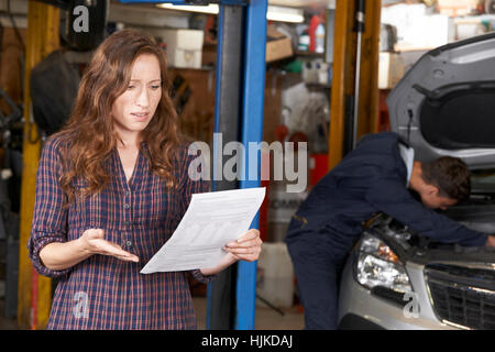 Shocked Female Customer Looking At Garage Bill - Stock Photo