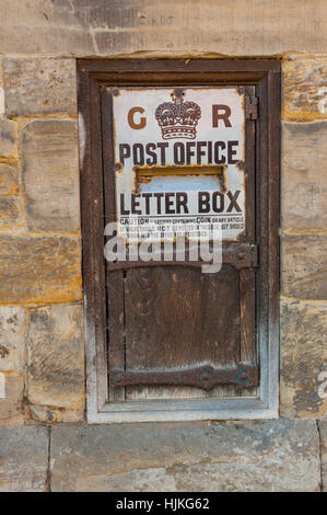 Old wooden post box in the wall of a building in Penshurst kent - Stock Photo