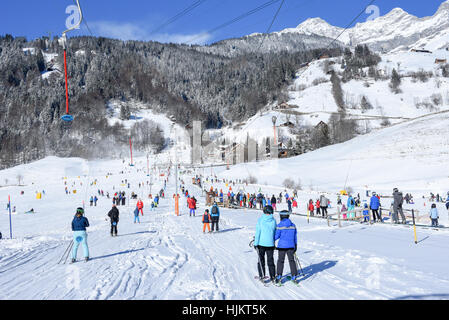 Engelberg, Switzerland - 6 January 2017: people going up with the ski lift and skiing down the slope of Engelberg - Stock Photo