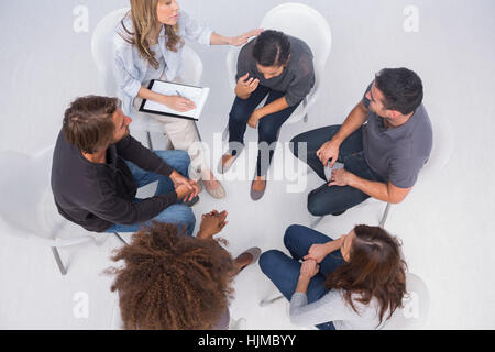 Therapist comforting her patient crying during group therapy - Stock Photo