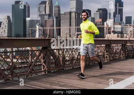 USA, New York City, man running on Brooklyn Brige - Stock Photo