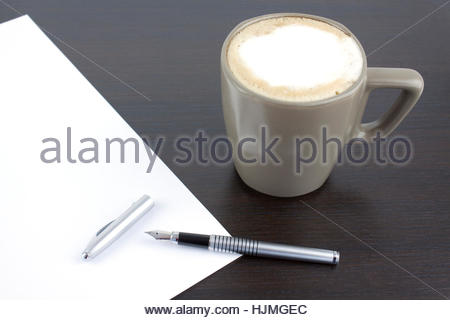 Pen and white sheet on a brown table - Stock Photo