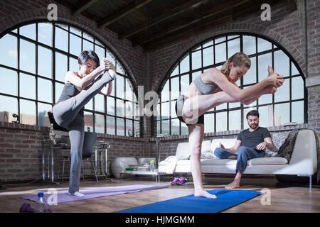 Two women doing yoga exercise in studio - Stock Photo